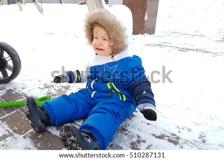 Cute toddler boy fell on winter park road with snow