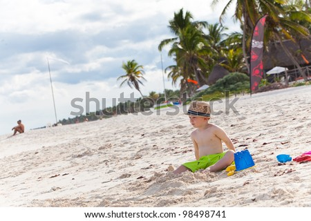 Cute toddler boy in a straw hat on a tropical beach - stock photo
