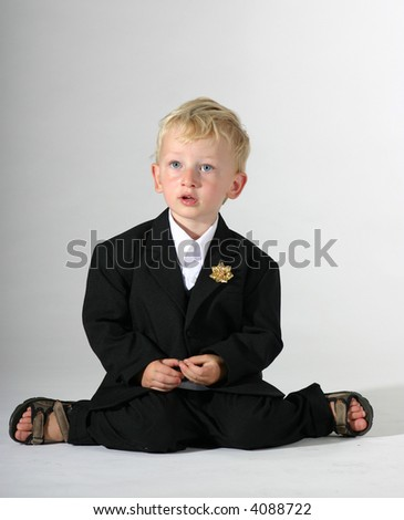 Cute toddler boy in black suit pretending to be a groom
