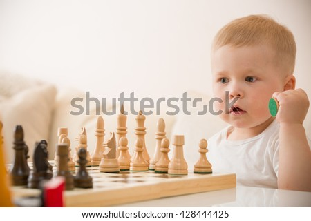 Cute toddler boy playing chess in the room. Little clever child playing chess at home. Education concept. Preschooler with chess. - stock photo