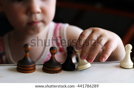 Cute toddler boy playing chess, soft focus