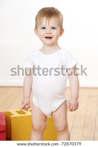 Cute toddler boy playing with colorful blocks on floor.