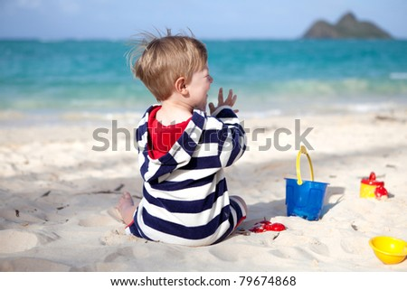 Cute toddler boy playing with sand toys on a tropical beach - stock photo