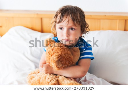 Cute toddler boy resting in a bed with teddy bear