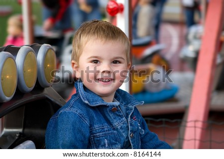 Cute toddler boy riding a car on a merry-go-round