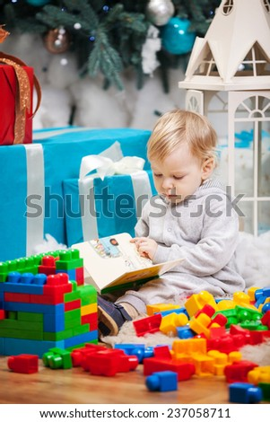 Cute toddler boy sitting at Christmas tree and reading book - stock photo