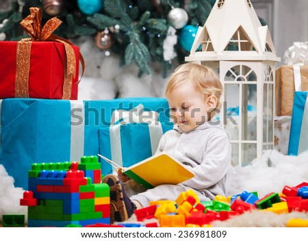 Cute toddler boy sitting at Christmas tree and reading book. Building blocks scattered around. - stock photo