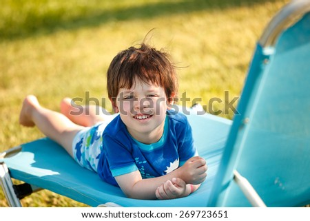 Cute toddler boy sitting on a sunbed by a swimming pool - stock photo