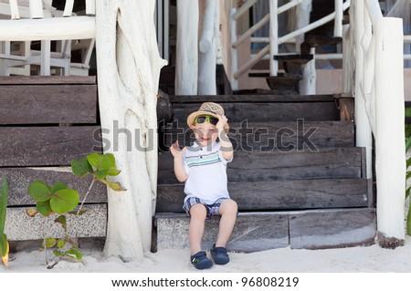 Cute toddler boy sitting on the stairs of a beach cafe - stock photo