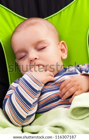 Cute toddler boy sleeping in a baby lounger, sucking his fingers