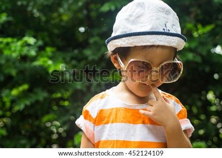 Cute toddler boy wearing sunglasses in the park - stock photo