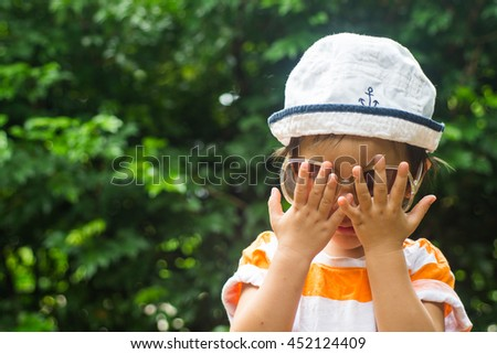 Cute toddler boy wearing sunglasses playing hide and seek  in the park - stock photo