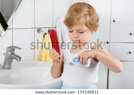 Cute toddler boy with blue eyes and blond hair brushing his teeth at home