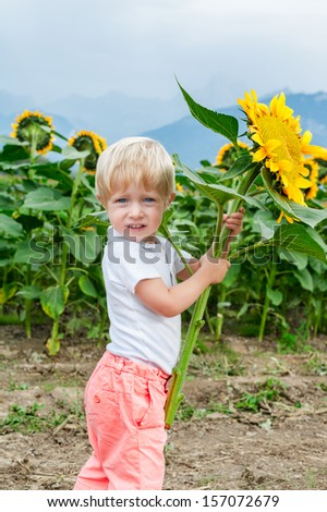 Cute toddler boy with sunflower in his hands outdoors portrait