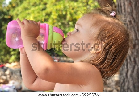 Cute toddler drinking water - stock photo
