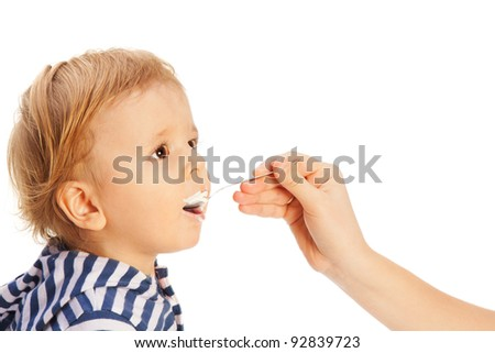 Cute toddler eat cottage cheese from spoon
