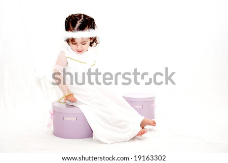 cute toddler girl dressed in angel costume sitting on gift boxes against white background - stock photo