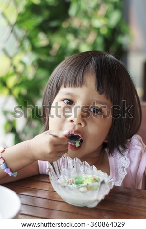 Cute Toddler Girl Eating Ice-Cream on a spoon - stock photo