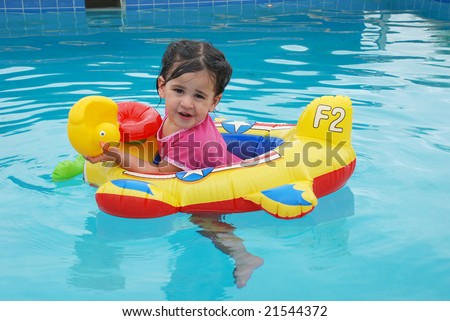 Cute toddler girl floating in a toy plane inflatable in swimming pool playing with a rubber ducky - stock photo