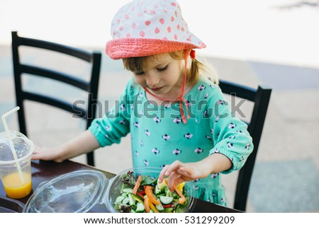 Cute toddler girl having her lunch raw vegetables sitting in a wooden chair