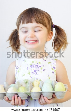 Cute toddler girl holding a carton of Easter eggs - stock photo