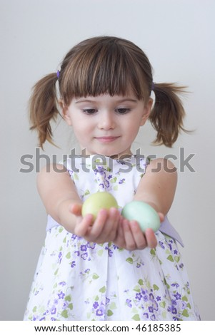 Cute toddler girl holding two colorful Easter eggs in her palms - stock photo