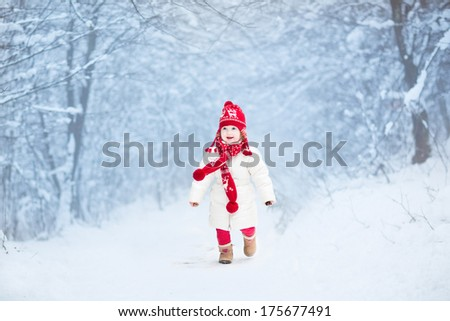 Cute toddler girl in a white warm jacket and red knitted hat and scarf running in a snowy winter park - stock photo