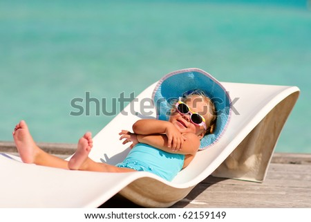 cute toddler girl in bikini, hat and sunglasses lyiing on a lounge and relaxing in tropic ocean background - stock photo