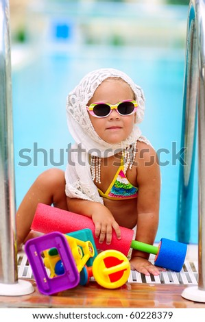 cute toddler girl in sunglasses and playing near pool outdoor - stock photo