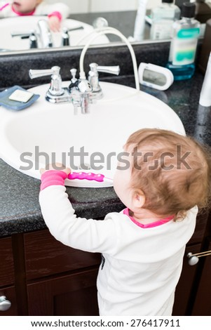 Cute toddler girl learning how to brush her teeth.