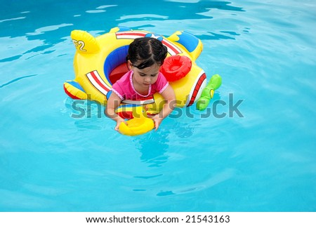 cute toddler girl on inflatable plane in swimming pool