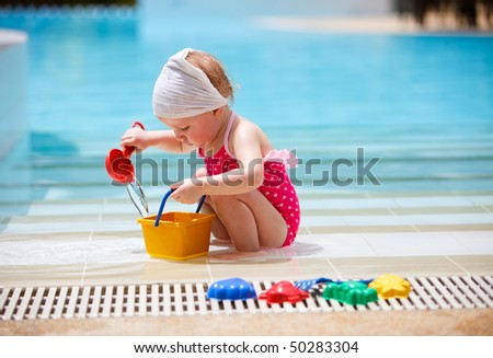 Cute toddler girl playing in swimming pool - stock photo
