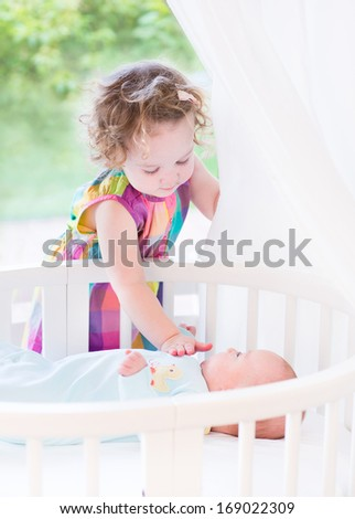 Cute toddler girl playing with her newborn baby brother laying in a white round crib next to a big window with garden view - stock photo
