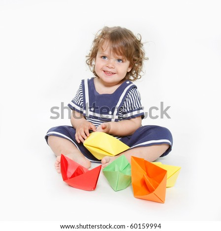 cute toddler girl playing with paper boats - stock photo