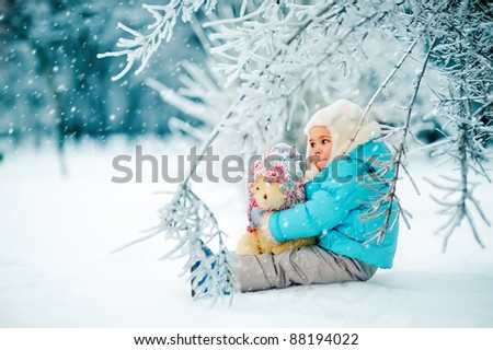 Cute toddler girl playing with teddy bear in winter park - stock photo
