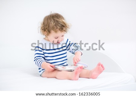 Cute toddler girl reading a book sitting in a white bedroom - stock photo