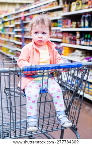 Cute toddler girl sitting in shopping cart at the grocery store.