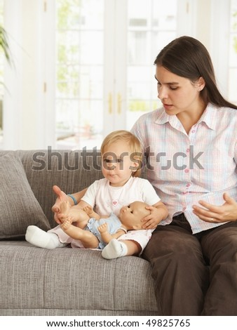 Cute toddler girl sitting on sofa with mother at home.