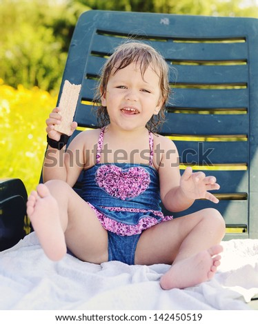 cute toddler girl sitting on sun lounger and eating crisp bread - stock photo