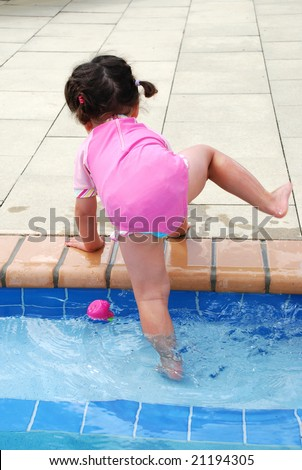cute toddler girl stepping out of swimming pool - stock photo