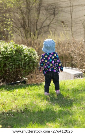 Cute toddler girl wearing hat on a sunny day - stock photo