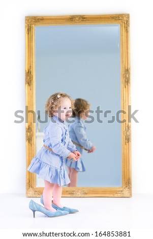 Cute toddler girl with beautiful curly hair wearing a blue dress is putting on her mother's high heels shoes standing at a big mirror with a wooden frame in a white bedroom at home - stock photo