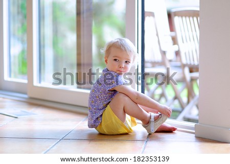 Cute toddler girl with blonde curly hair putting on her shoe sitting on the tiles floor next to a big opened sliding door window with garden view getting ready to play outdoors - stock photo