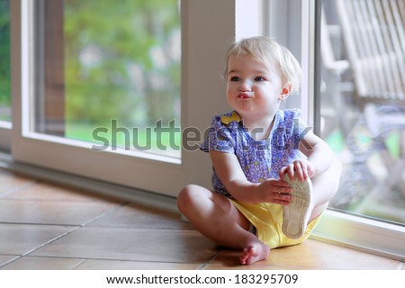 Cute toddler girl with blonde curly hair putting on her shoe sitting on the tiles floor next to a big sliding door window with garden view getting ready to play outdoors - stock photo