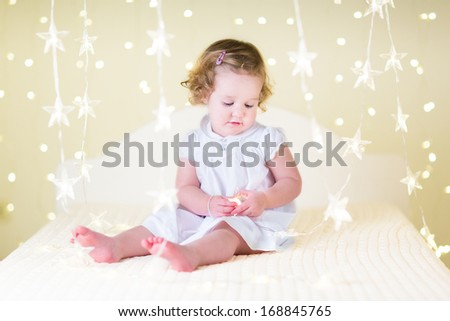 Cute toddler girl with curly hair in a white dress playing with soft warm Christmas lights