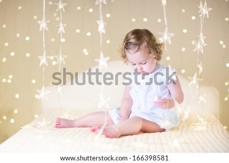 Cute toddler girl with curly hair wearing a white dress playing on a white bed with warm Christmas lights