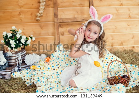 Cute toddler girl with easter bunny fancy ears sitting on colorful plaid and celebrating easter - stock photo