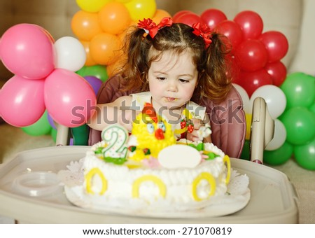 cute toddler girl with her birthday cake - stock photo
