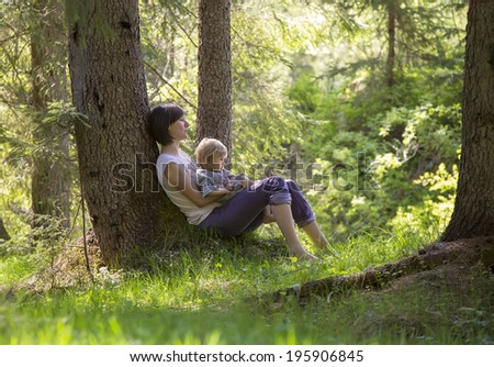 cute toddler girl with her mother in  sitting under a tree in a forest - stock photo