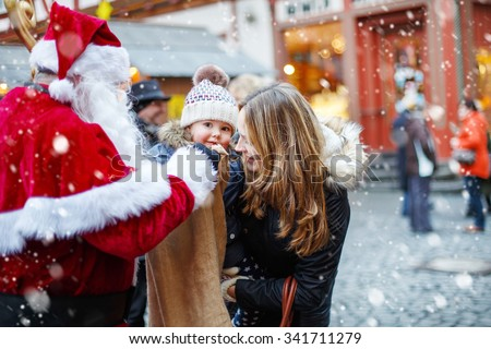 Cute toddler girl with mother on Christmas market. Funny happy kid taking gift from bag of Santa Claus. holidays, christmas, childhood and people concept. Happy family during snowfall on winter day. - stock photo